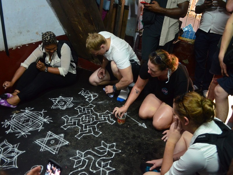 Guests Trying Floral patterns or Kolam in Kochi Sightseeing Tour